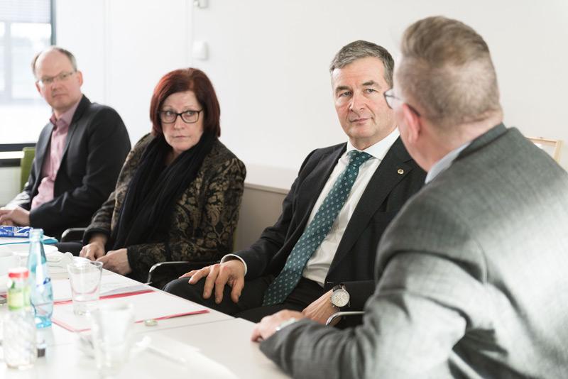 3 Männer und eine Frau im Gespräch an einem Konferenztisch.