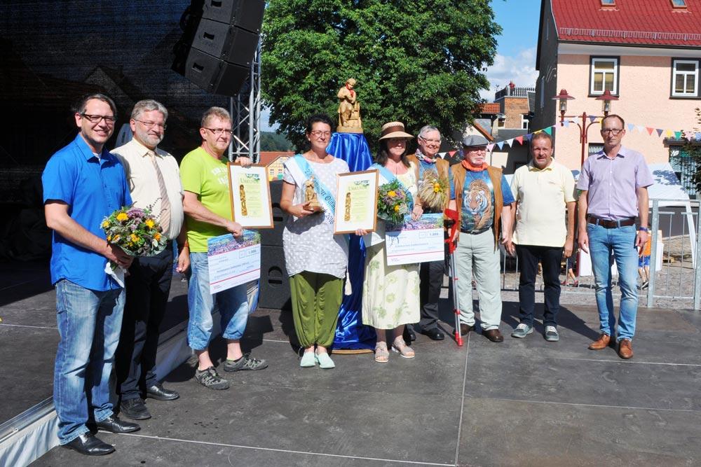 Die neuen und alten Preisträger des Wandernden Heilkräuterpreis der Stadt Königsee-Rottenbach sowie Vertreter von Stadt sowie Hofmann & Sommer stehen auf einer Büchne.