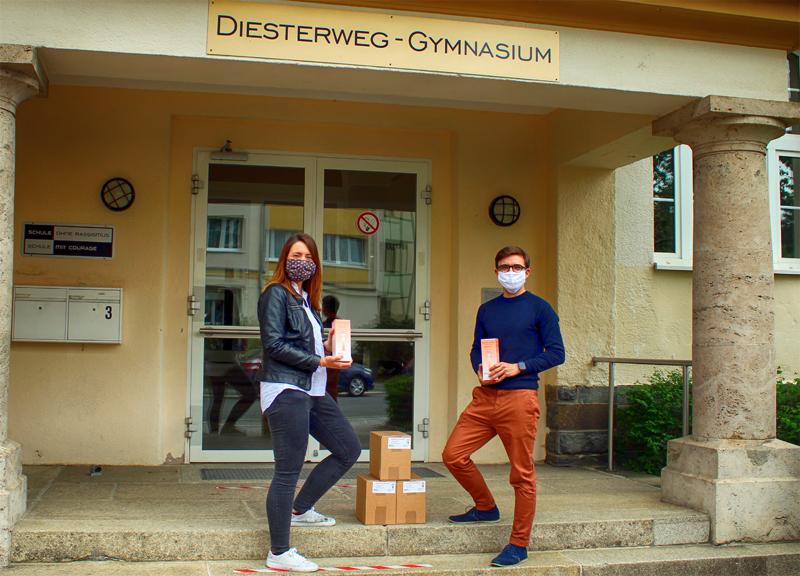 Eine Frau und ein Mann in Maske stehen posieren vor einem Schuleingang