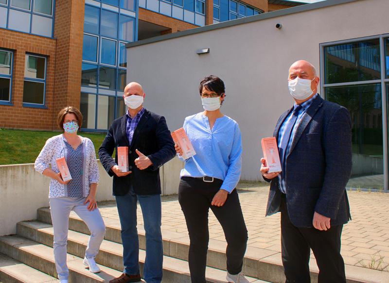 2 Männer und 2 Frauen mit Masken vor dem Königseer Schulkomplex