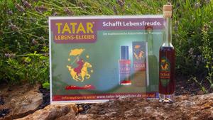 Eine Flasche mit TATAR Lebens-Elixier und ein Werbeschild vor einem Kräuterbeet.