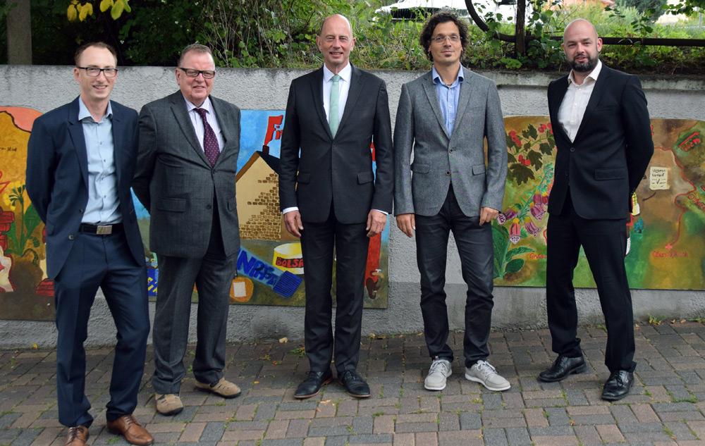 Fünf Männer in Anzügen vor den Schautafeln zur Firmengeschichte von Hofmann & Sommer.
