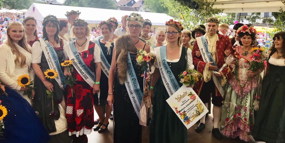 Verschiedene Thüringer Ehren-Majestäten präsentieren sich auf einer Bühne.
