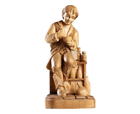 Eine geschnitzte Holzfigur, die einen Buckelapotheker beim Herstellen von Olitäten zeigt.